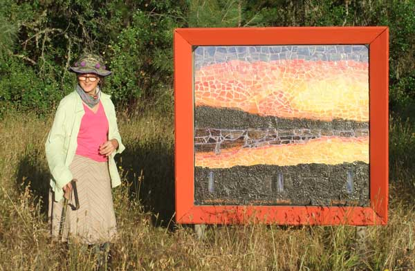 "Intallation picture of Artist, Alicia Lee Farnsworth and her 4'x4' hand made, custom glazed and grouted landscape mosaic called ""Clearlake Winter Sunset' installed at the Middletown County Trailside park as part of Ecoartarts of Lake County Sculpture Walk 2015. from June-October"
