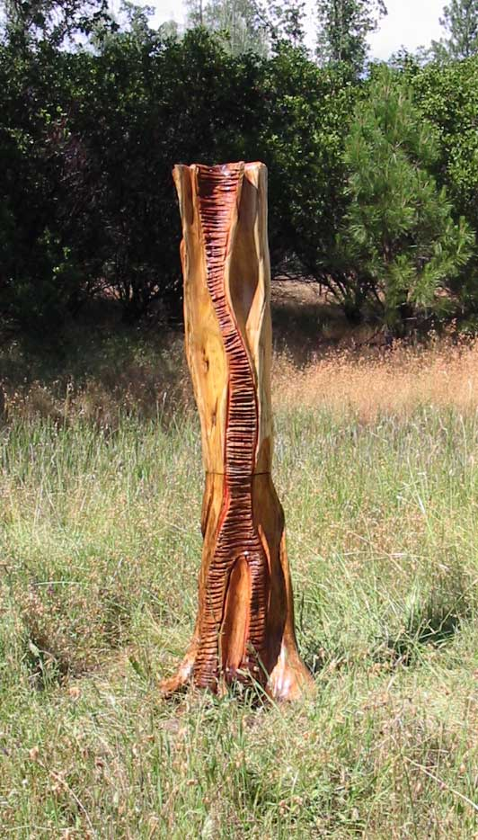 A 6 foot Carved Abstract Wood Sculpture, Carved from Pacific Willow with Tung oil finish and red painted accents in some of the carved grooves